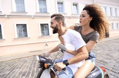 Happy young couple having fun on a scooter stock image