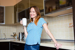 Happy cheerful cute young pregnant woman standing on kitchen Stock Photo