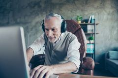 Happy cheerful delightful joyful funny employer is using his upd. Ated computer for playing games and listening to music via headphones Stock Images