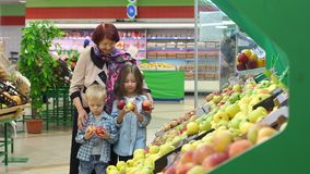 Grandmother with her grandchildren to buy food and fruit at the supermarket. Happy cheerful elderly woman in her grandchildren to buy food and fruit at the stock video