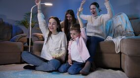 Happy cheerful family celebrating victory or football goal while watching TV at night