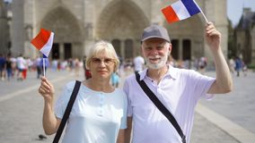 Happy family enjoying vacation. Seniors standing near Notre Dame of Paris. Waving French flags. Happy cheerful family enjoying vacation. Seniors standing near stock video