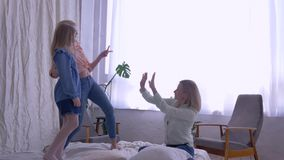 Happy cheerful family, joyful adult and small girls daughters sing and fool around for Mama while having fun. Entertainment on bed at home on weekends stock footage