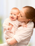 Happy cheerful family. Mother and baby kissing Royalty Free Stock Photos