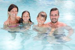 Cheerful family portrait in swimming pool in summer vacation. Happy cheerful family portrait in swimming pool in summer vacation Stock Image
