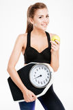 Happy cheerful fitness woman holding weight scales and green apple Royalty Free Stock Images