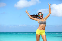 Happy cheerful fitness woman in sunglasses winning arms up doing v hand signs. Fit girl with slim body on sunny beach with raised arm showing peace sign in Royalty Free Stock Photo