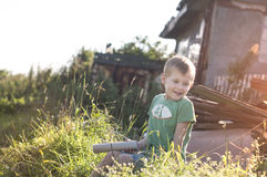 Happy cheerful funny little child sitting on grass. Autumn, happy cheerful funny little child sitting on grass in countryside on sunset Stock Photos