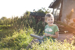 Happy cheerful funny little child sitting on grass Royalty Free Stock Images