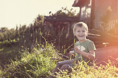 Happy cheerful funny little child sitting on grass. In countryside on sunset Stock Image