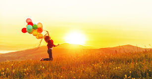 Happy cheerful girl with balloons running across meadow at sunse. T on nature in summer Royalty Free Stock Images