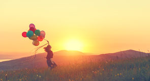 Happy cheerful girl with balloons running across meadow at sunse Stock Photos