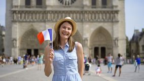 Cheerful girl enjoying vacation. Tourist in hat standing near Notre Dame of Paris. Waving French flag