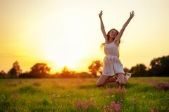 Happy cheerful girl is jumping on nature over the summer sunset royalty free stock photography