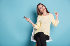 Happy cheerful girl listening music over blue background Stock Photos