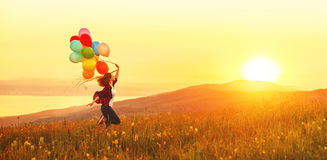 Happy Cheerful Girl With Balloons Running Across Meadow At Sunset In Summer Royalty Free Stock Images