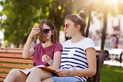 Happy cheerful girls are in the park to enjoy summer atmosphere and read latest news in world. Young beautiful friends give funny. Comments to each photo and stock photography
