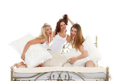 Happy cheerful girls. Pyjamas party. Happy cheerful girls having fun sitting on the bed on a white background Stock Photography
