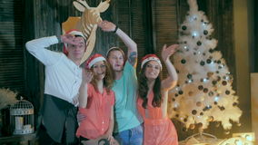 Happy, cheerful group of friends at Christmas party. Greeting into camera, having fun smiling celebrating new year`s eve stock video