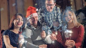 Happy cheerful group of friends at new year christmas party lighting sparklers having fun smiling celebrating new year`s stock video footage