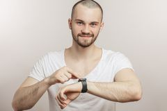 Happy, cheerful guy is touching the screen of his smartwatch royalty free stock photos