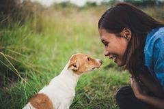 Happy cheerful hipster girl playing with her dog in the park during sunset. Vintage of young woman with her dog. stock photography
