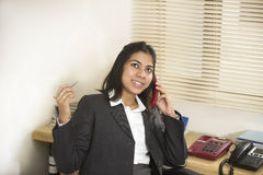 Happy and cheerful Indian businesswoman talking on telephone Royalty Free Stock Photos