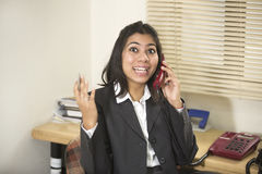 Happy and cheerful Indian businesswoman talking on telephone Royalty Free Stock Image