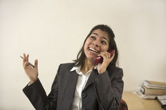 Happy and cheerful Indian businesswoman talking on telephone Royalty Free Stock Photo