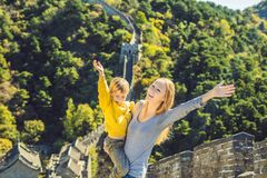 Happy cheerful joyful tourists mom and son at Great Wall of China having fun on travel smiling laughing and dancing stock photos