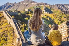 Happy cheerful joyful tourists mom and son at Great Wall of China meditate on vacation trip in Asia. Chinese destination stock photo