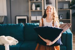Happy cheerful kid girl posing with pillow, cozy couch behind in modern living room Stock Photos