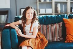 Happy cheerful kid girl posing with pillow, cozy couch behind in modern living room Stock Image