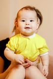 Happy cheerful kid in yellow shirt, portrait. Looking straight into camera, standing with support of mother at Royalty Free Stock Photos