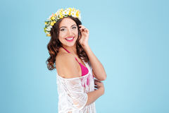 Happy cheerful lady wearing flower diadem over blue background stock photography