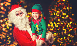 Happy cheerful laughing child elf helper and Santa Claus at Chri. Happy cheerful laughing child elf helper in the hands of Santa Claus at Christmas Stock Photo
