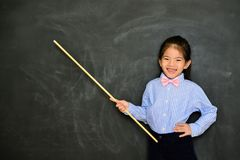 Happy cheerful little girl dressed as teacher. Standing in blackboard background and using stick pointing teaching student stock image