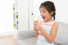 Happy cheerful little girl kid holding ice cream. Snack sitting on living room sofa and feeling surprised during summer season holiday Stock Photography