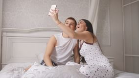 Happy cheerful loving couple making selfie in bed, young attractive guy and girl sitting in pajamas. People`s attitudes Stock Photos