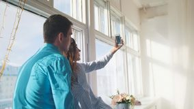 Happy cheerful loving couple making selfie on window, young attractive guy and girl. People`s attitudes Stock Photos