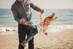 Happy cheerful loving family, father and little daughter playing on beach, young father is holding his kid upside down Royalty Free Stock Photography