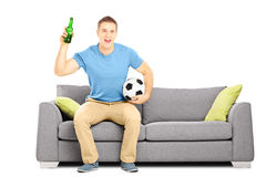 Happy cheerful male sport fan with ball and beer watching sport Stock Photos