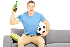 Happy cheerful male sport fan with soccer ball and beer bottle w Stock Photo