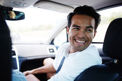 Happy cheerful male talking with passengers while sitting in comfortable automobile Stock Image