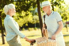 Happy cheerful man holding a picnic basket. Pleasant picnic. Happy cheerful elderly men holding a picnic basket and looking at his wife while having a picnic Royalty Free Stock Photo