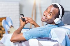 Happy cheerful man smiling to you. Positive mood. Happy cheerful handsome man wearing headphones and smiling to you while listening to music royalty free stock image