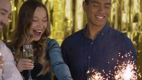 4 happy cheerful people at a party light a sparkler. a group of laughing people of mixed race on a gold background. HD stock footage