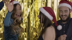 4 happy cheerful people at a party in red Santa Claus hats dance funny at a party. A group of laughing people of mixed stock footage