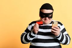 Happy cheerful plump hacker with a bank card and mobile phone. Isolated on the yellow Background. crime, illegal business copy space, isolated yellow background royalty free stock images