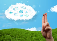 Happy smiley fingers looking at cloud with blue social icons and. Happy cheerful smiley fingers looking at cloud with blue social icons and smybols royalty free stock photos